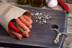 Raw homemade sausages of lamb with rosemary and chili pepper in a paper envelope on a black wooden Board.  Royalty Free Stock Images