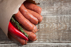 Raw homemade sausages of lamb with rosemary and chili pepper in a paper envelope on wooden table. Stock Photo