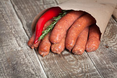 Raw homemade sausages of lamb with rosemary and chili pepper in a paper envelope on wooden table. Raw homemade sausages of lamb with rosemary and chili pepper Royalty Free Stock Image