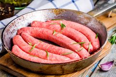 Raw homemade sausages in a pan with rosemary Stock Photography