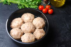 Raw homemade steamed meatballs with chicken and buckwheat. black concrete background. place for text. copyspace stock images