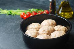 Raw homemade steamed meatballs with chicken and buckwheat. black concrete background. place for text. copyspace royalty free stock image