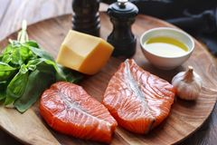 Salmon steaks with cheese and fresh ingredients. Raw humpback salmon steaks, cheese, rustic wooden background, above view. Fillet with fresh ingredients for Royalty Free Stock Photo
