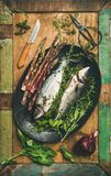 Raw incooked sea bass with herbs. Cooking fish dinner. Flat-lay of raw incooked sea bass with herbs and vegetables over rustic wooden background, top view stock image