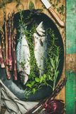 Raw incooked sea bass with herbs. Cooking fish dinner. Flat-lay of raw incooked sea bass with herbs and vegetables over rustic wooden background, top view stock photography