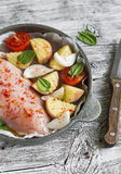 Raw ingredients - chicken breast, potatoes, onions, tomatoes. For cooking chicken breast with vegetables. Royalty Free Stock Photography