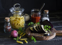 Raw ingredients for cooking Italian pasta with eggplant. Penne pasta, eggplant, onion, tomato sauce, spices and herbs. On a dark wooden background. Healthy Royalty Free Stock Photo