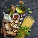 Raw ingredients for cooking pasta with porcini - dried porcini mushrooms, spaghetti, cream, garlic, parsley, basil, olive oil and Royalty Free Stock Photos