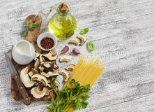 Raw ingredients for cooking pasta with porcini mushrooms - dried porcini mushrooms, spaghetti, cream, garlic, parsley, basil, oliv Stock Photography