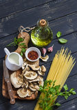 Raw ingredients for cooking pasta with porcini mushrooms - dried porcini mushrooms, spaghetti, cream, garlic, parsley, basil, oliv Stock Images
