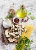 Raw ingredients for cooking pasta with porcini mushrooms - dried porcini mushrooms, spaghetti, cream, garlic, parsley, basil, oliv Stock Photos