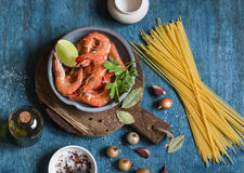 Raw ingredients for cooking - prawns and spaghetti on a wooden background, top view. Flat lay Royalty Free Stock Photo