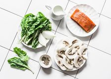 Raw ingredients for cooking salmon with creamy spinach mushrooms sauce on a light background, top view. Salmon florentine lunch. Spinach, mushrooms and salmon stock photography