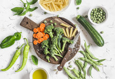 Raw ingredients for cooking vegetarian lunch - dry pasta, fresh broccoli, zucchini, green peas and beans, carrots, olive oil. On a light background, top view Royalty Free Stock Image