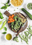 Raw ingredients for cooking vegetarian lunch - dry pasta, fresh broccoli, zucchini, green peas and beans, carrots, olive oil. Royalty Free Stock Photos