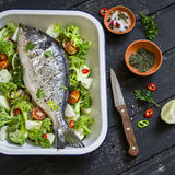 Raw ingredients - Dorado fish and vegetables - broccoli, zucchini, onions, peppers, lime and spices on a dark wooden surface Royalty Free Stock Image