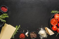 Raw ingredients for lasagna, pasta, vegetables on black. Copy space royalty free stock image