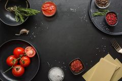 Raw ingredients for lasagna, pasta,vegetables and herbs on black. Copy space. Raw ingredients for lasagna, pasta,vegetables and herbs on black background. View royalty free stock image