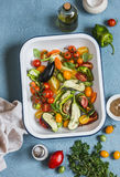 Raw ingredients for lunch - fresh chopped vegetables in the pan on a blue background, top view. Royalty Free Stock Photo