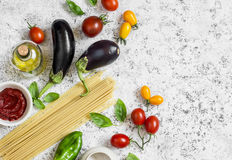 Raw ingredients for making pasta - spaghetti, eggplant, tomatoes, pepper, olive oil, tomato sauce and basil Stock Photos