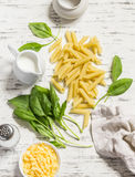 Raw ingredients for making pasta with spinach cream sauce - penne pasta, fresh spinach, cream, cheese and spices Royalty Free Stock Photos