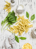 Raw ingredients for making pasta with spinach cream sauce - penne pasta, fresh spinach, cream, cheese and spices Royalty Free Stock Image