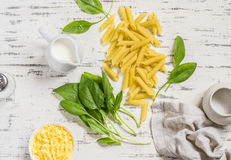 Raw ingredients for making pasta with spinach cream sauce - penne pasta, fresh spinach, cream, cheese and spices on a wooden Royalty Free Stock Images