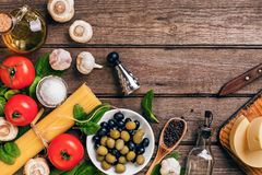 Raw ingredients for the preparation of Italian pasta, spaghetti, basil, tomatoes, olives and olive oil on wooden royalty free stock photography