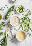 Raw ingredients - rice, cous cous, zucchini, green beans and peas, olive oil on a light background. Stock Photography