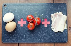 Raw ingredients for scrambled eggs, raw food formula, tomato eggs and bacon on a cutting board top view royalty free stock photos