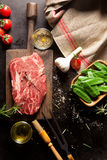Raw Ingredients for Steak Dinner. Still Life of Raw Ingredients for Preparing Dinner Meal - Raw Steak on Cutting Board, Snow Peas in Wooden Dish, Garlic Bulb and Royalty Free Stock Photo