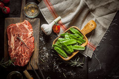Raw Ingredients for Steak Dinner. Still Life of Raw Ingredients for Preparing Dinner Meal - Raw Steak on Cutting Board, Snow Peas in Wooden Dish, Garlic Bulb and Stock Photos