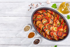 Raw ingredients for traditional French casserole, ratatouille to. Layered ratatouille in a baking dish, slices of zucchini, red bell pepper, chili, yellow squash stock photography