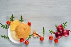Raw ingredients for veggie burger on the gray concrete background with free copy space. Vegetarian sandwich. Decorated with cherry tomatoes, onion, garlic and Royalty Free Stock Images