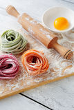 Raw italian color pasta and rolling pin Royalty Free Stock Photos