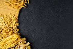 Raw Italian pasta fettuccine, paccheri, farfalle, spaghetti. Penne, conchiglie on a dark background. Flat lay Stock Images