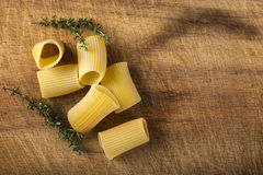 Raw Italian pasta and some thyme on wood with copy space Royalty Free Stock Image