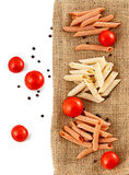 Raw Italian pasta with tomatoes and black pepper on material bac Stock Photography