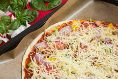 Raw Italian Pizza. Uncooked pizza with ham, basil and vegetables on a baking sheet, close-up as top view for Italian food Stock Image