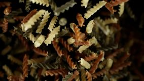 Raw italian rotini pasta flies. Pile of multicolored pasta macaroni bouncing. Raw italian rotini pasta flies after being exploded. Pile of multicolored pasta stock video footage