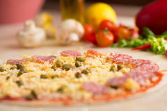 Raw italian salami pizza on table Royalty Free Stock Photo