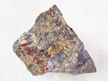Raw jaspilite stone on white. Macro shooting of natural mineral rock specimen - raw jaspilite (ferruginous quartzite) stone on white marble background stock photo