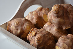 Raw Jerusalem artichokes in wooden container Stock Photos