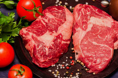 Raw juicy meat Ribeye on a cutting board with tomatoes, parsley and spices. Dark wooden background Stock Photography