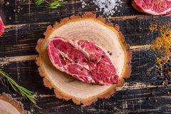 Raw juicy meat steak on dark wooden background ready to roasting Royalty Free Stock Photos