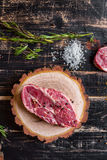 Raw juicy meat steak on dark wooden background ready to roasting Stock Photography