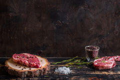 Raw juicy meat steak on dark wooden background ready to roasting Stock Images