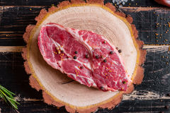 Raw juicy meat steak on dark wooden background ready to roasting Royalty Free Stock Image
