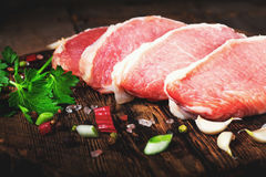Raw juicy meat steaks ready for roasting on a black chalk board Royalty Free Stock Photography