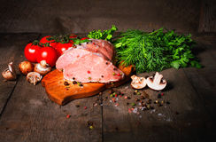 Raw juicy meat steaks ready for roasting on a black chalk board. Stock Photo